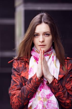 Beautiful girl in a red cloak praying