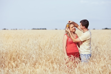 Guy catches a flower girl in a wheat field