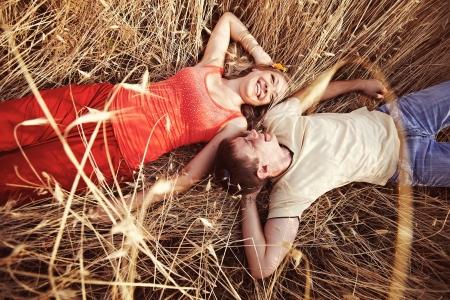 A man and a woman are in a wheat field