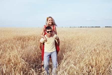A man carries a girl in a wheat field