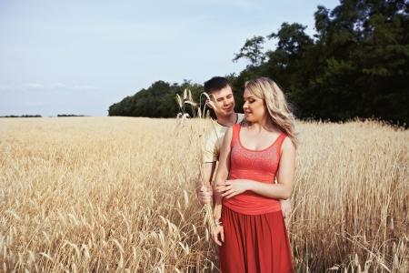 Man giving a bouquet of ears girl in a wheat field