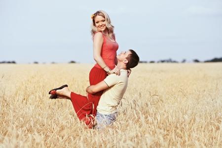 raises: Man raises his hands on the girl on wheat field