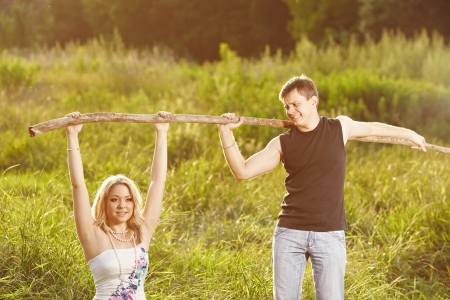Young couple support each other, holding on to a tree on a background of green