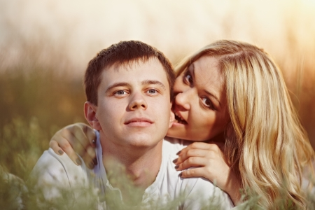 oung couple lying on the sunset background  Man bites woman s ear