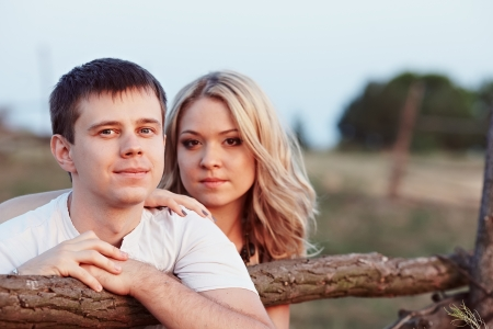 Young couple at sunset near a wooden fence