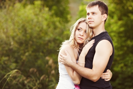 Man and woman embracing and looking into the distance Stok Fotoğraf