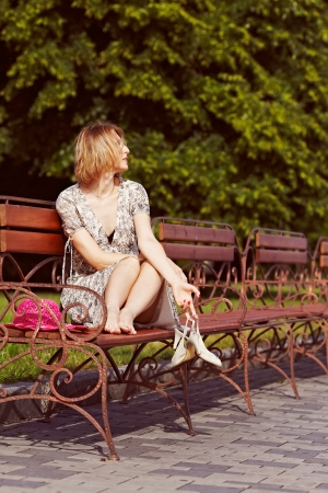 Beautiful girl takes off shoes, sitting on the bench.