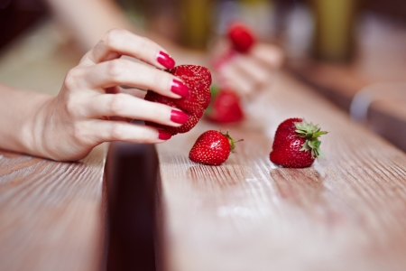 The girl picks strawberries on the table by hand Stock Photo