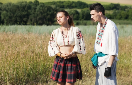 Married couple in traditional costumes quarrels in nature Stock Photo
