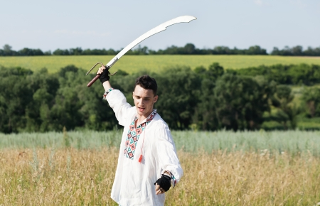 Slavic warrior in national dress with sword unsheathed