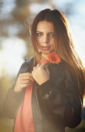 Beautiful girl holding a flower in the autumn forest