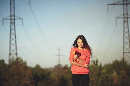 Beautiful girl holding a flower against the masts of power lines Stok Fotoğraf