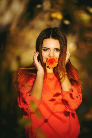 Beautiful girl holding a flower in his mouth in the autumn forest