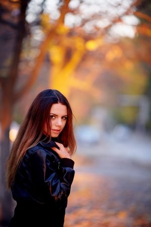 Pretty girl in a black jacket at sunset Stock Photo