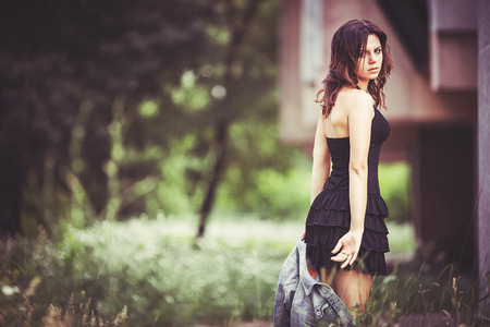 Beautiful girl in black skirt holding hands in jeans jacket Stock Photo
