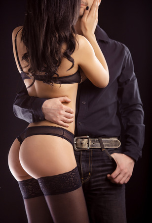 On dark background girl in lingerie with man in shirt Stock Photo