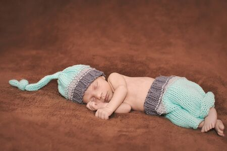 Baby boy sleeping on a carpet in a woolen hat Stock Photo