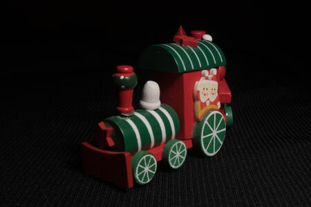 Red children`s Christmas train on a black background. Christmas magic city. Paper tree and star, decoration for the holiday. New Year's toy.