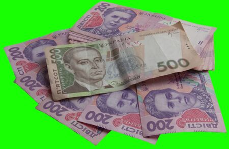 A lot of money Ukrainian hryvnia on a gren background with copy space