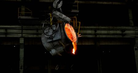 Smelting orange metal in a metallurgical plant. Liquid iron from the ladle 版權商用圖片