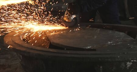Working in a mask and headphones cleans joints angle grinder on metal parts blanks