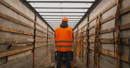 warehouse worker driver in uniform loading cardboard boxes by forklift stacker loader Banque d'images