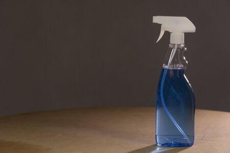 Blue Glass Cleaner Spray Spraying Dispersion Pulverizer. On a dark background Archivio Fotografico