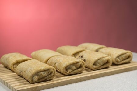 Raw rolled pancakes with filling ready to be roasted. On a red background