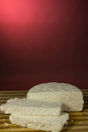 Italian soft cheese made from cow's milk, On a burgundy background