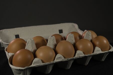 Egg tray with chicken eggs and decorative bunny on grey and black background