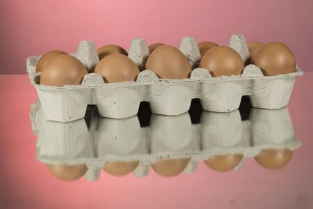 Closeup Eggs with the blue refrigerator 's tray on black mirror background. Mirror pink background