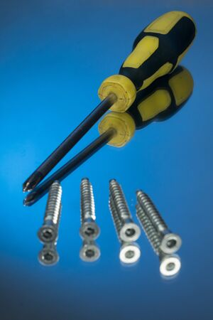 Screwdriver and wood screws isolated on blue background. mirror reflection background.