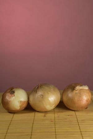 Three onions on bamboo board cutting, red background Фото со стока