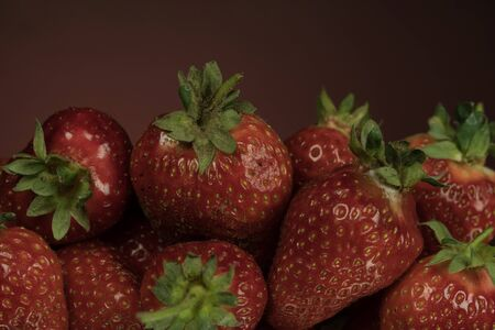 Handful of ripe strawberries on a mirror background. Close-up. Strawberries are rich in vitamins