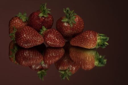 A tasty red ripe strawberry on a mirror. Isolated close-up detail shot, red background. Strawberries are rich in vitamins, trace elements and antioxidants.