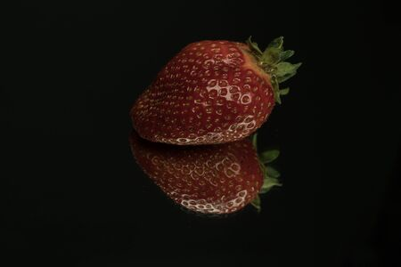 A tasty red ripe strawberry on a mirror. Isolated close-up detail shot, black background. Strawberries are rich in vitamins, trace elements