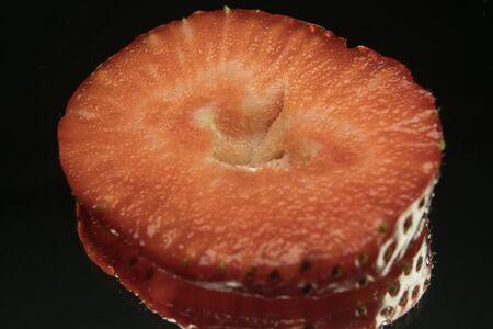 Strawberry slices, macro shot, black mirror background