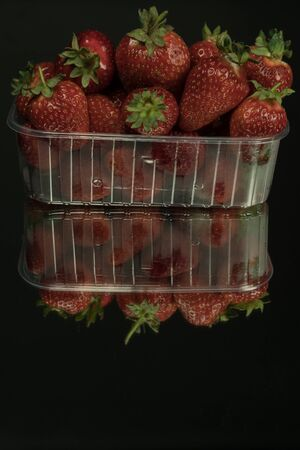 Fresh strawberries in a clear plastic box. On a mirror black background. Strawberries are rich in vitamins, trace elements and antioxidants.