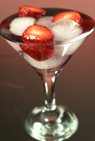 Cold cocktail with ice and strawberries seeds. Mirror red background