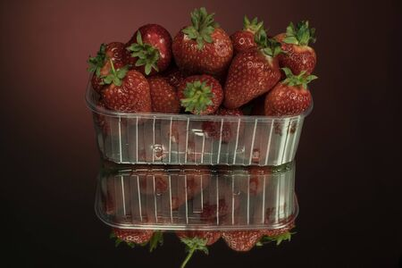 Fresh strawberries in a clear plastic box. On a mirror red background. Strawberries are rich in vitamins, trace elements and antioxidants.