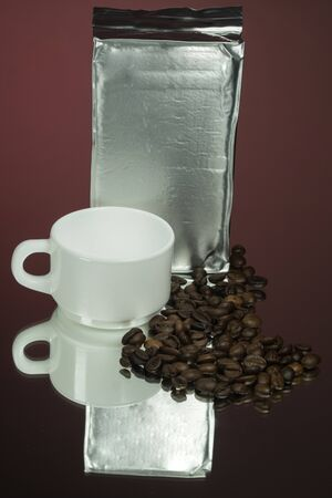 Silver coffee pack, white mug, coffee grains on a mirror red background