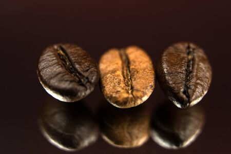 Three roasted coffee beans in a row, horizontal. Extreme close up, macro photography, selective focus. Background deep red, foreground textured black with light effects. Space for copy or text.