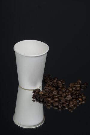 Paper cup of coffee with smoke and coffee beans. Mirror black background