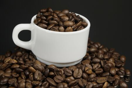 White mug with coffee grains sprinkled with coffee grains on a dark background