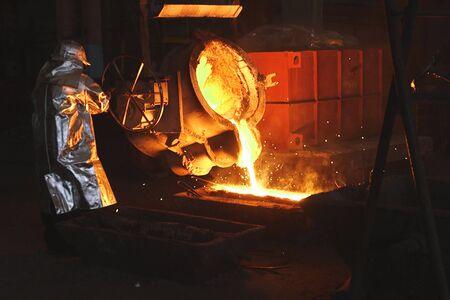 Le métal en fusion est versé dans le moule. Four de fusion pour fonte et acier et métal liquide.