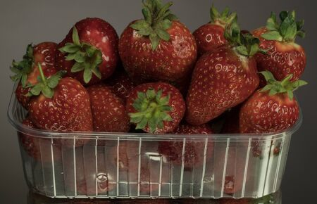 red ripe strawberry in plastic box of packaging on table