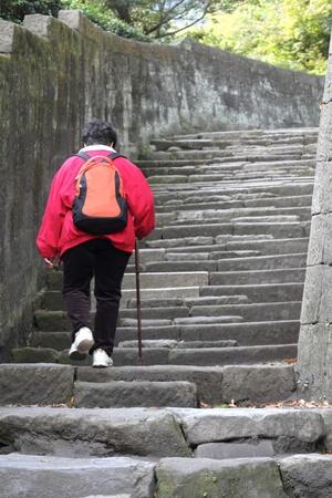 지팡이는 계단을 올라가고 노인 여성