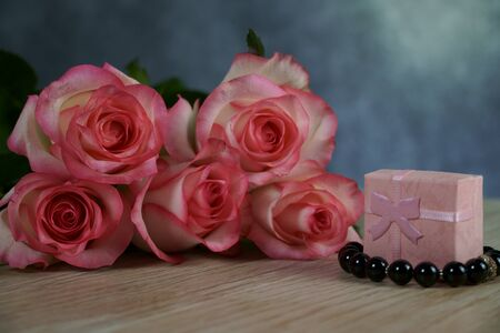 dolce vita roses with pink present box on wood background Standard-Bild