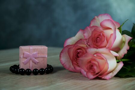 dolce vita roses with pink present box on wood background