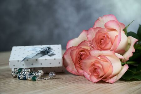 dolce vita roses with dotted white present box on wood background Standard-Bild